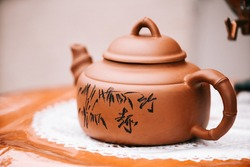 Chinese brown teapot and teacups on the wooden trivet isolated on white