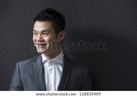Chinese Business man leaning on a black wall. Handsome young Chinese business man leaning against a black wall and looking away.