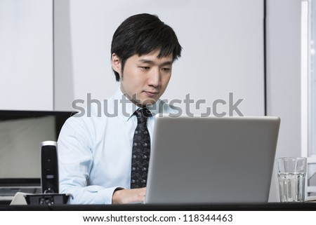 Chinese business man working on his laptop in an office.