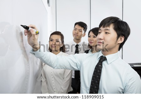 Chinese business man writing on a whiteboard with his team around him.