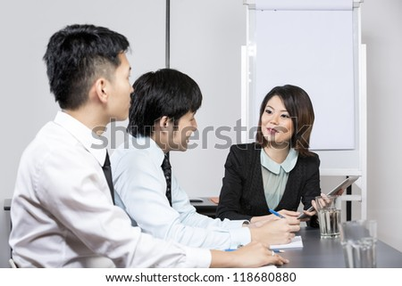 Chinese Business woman leading a meeting in the office.