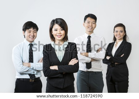 Chinese business woman with her team out of focus behind her.