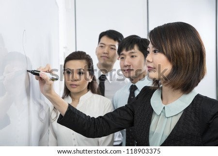 Chinese business woman writing on a whiteboard. Her team are behind her out-of-focus.