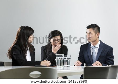 Chinese business woman yawning during a business meeting in front of work colleges