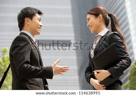 Chinese Businessman And Businesswoman Having Discussion Outside Office
