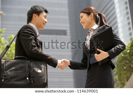 Chinese Businessman And Businesswoman Shaking Hands Outside Office