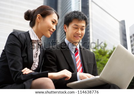 Chinese Businessman And Businesswoman Working On Laptop Outside Office