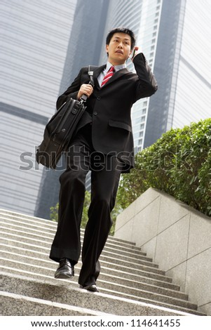 Chinese Businessman Rushing Down Steps On Mobile Phone