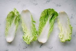 Chinese cabbage leaves on a white background, top view.