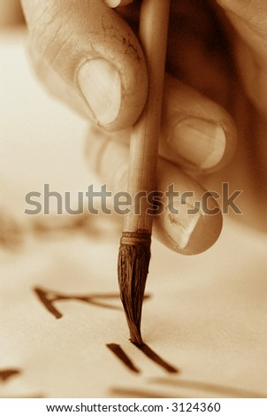 Chinese calligraphy. Close up of the rough fingers of an artist and brush. High ISO black and white sepia image.