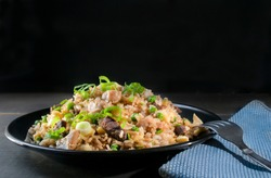 Chinese Cantonese fried rice with chicken, peas and chives on top, in a black background. Asian food concept