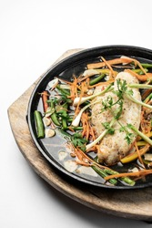 chinese cantonese style steamed spicy fish fillet with vegetables on hot plate
