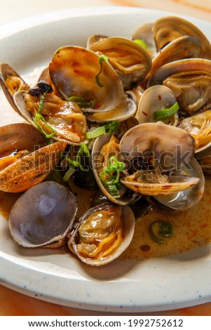 Chinese clams with black bean sauce garnished with green onions