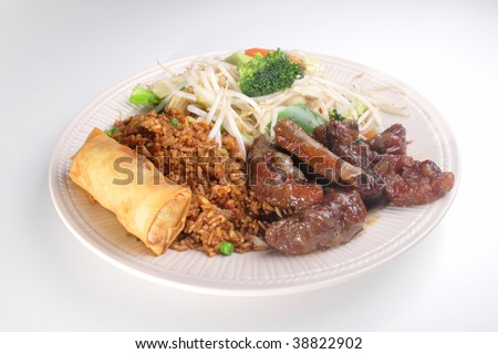Chinese combination plate with spring roll, chicken fried rice, mixed vegetable chop suey, and honey garlic ribs.