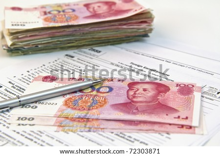Chinese currency, tax form, silver pen shoot under soft lights