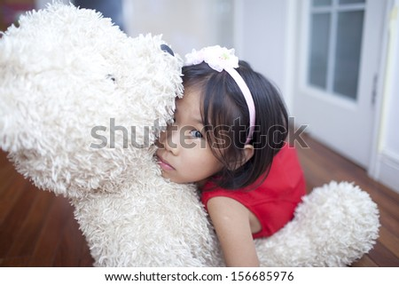 Chinese cute girl with teddy bear  at home