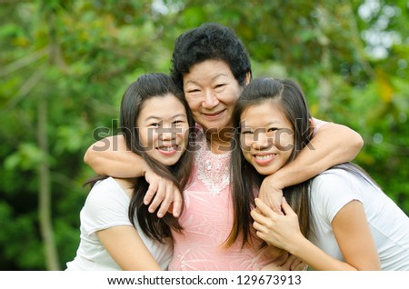 chinese daughter and mother on green outdoor - stock photo