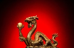 Chinese Dragon holding a gold Sphere and a red background