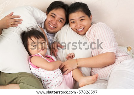 Chinese family having fun on bed showing love and togetherness