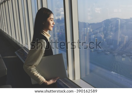 Chinese female successful entrepreneur with laptop computer is standing in modern office interior near skyscraper window with copy space area for your advertising text message or promotional content