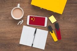 Chinese flag, Chinese textbook, Smartphone, wireless headphones on a wooden brown table, concept of learning a foreign language