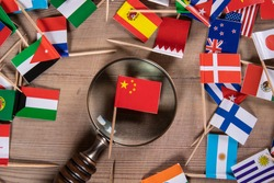 Chinese flag. Economic growth, Imports and Exports, Armaments and Security concept. Magnifying glass and flags of different countries