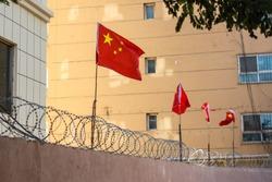 Chinese flags on barbed wire wall in Kashgar (Kashi), Xinjiang, China.
