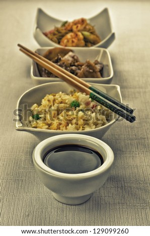 Chinese food composition with cantonese rice, noodles with prawns and beef with mushrooms