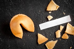 Chinese fortune cookie with prediction on dark background top view