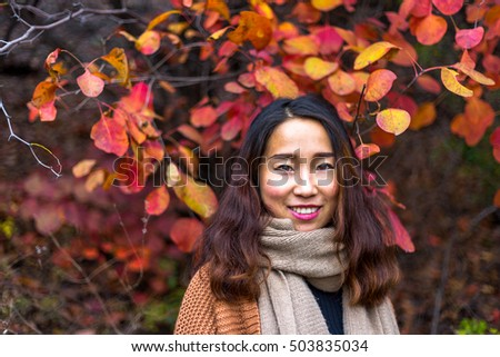 Chinese girl in the middle of red maple tree leaves, in the Red leaves valley, Jinan, Shandong province, China. #503835034