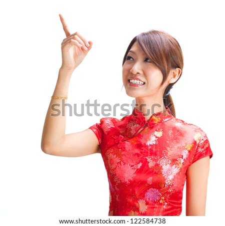 Chinese girl in traditional Chinese cheongsam pointing at blank space, isolated on white background