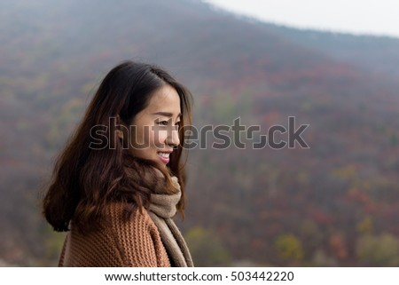 Chinese girl looking the red maple tree leaves from the pagoda in the Red leaves valley, Jinan, Shandong province, China. #503442220