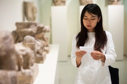 Chinese girl with interest using guidebook at ancient sculptures in museum