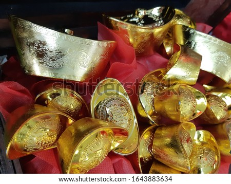 Chinese gold pieces with red cloth background. Chinese New Year decorations. The word on the gold is the combination of the Chinese words '招財進寶', meaning good luck and wealth.  ストックフォト ©