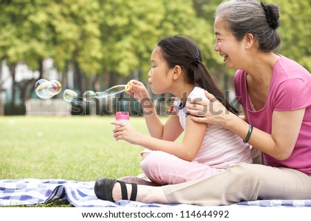 Chinese Grandmother With Granddaughter In Park Blowing Bubbles