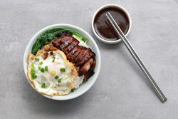 Chinese grilled sweet pork rice served with fried egg and vegetable.
