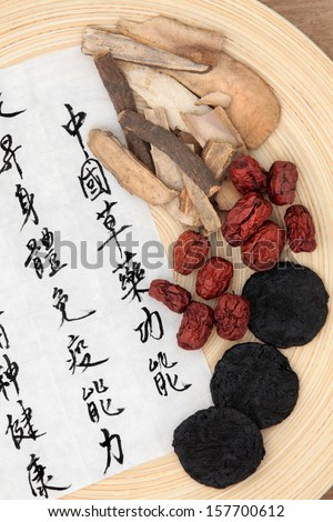 Chinese herbal medicine of rehmannia, peony bark and red dates with mandarin calligraphy on rice paper. Translation describes the functions to maintain health and balance energy.