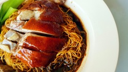 Chinese Hong Kong authentic Crispy Roasted Duck Noodles with Dark Soy Sauce and Steamed Vegetables