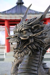 Chinese, iron dragon. Dragon statue on the background of a red Chinese house