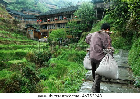 Chinese laborer carrying seed to rice farm on the mountains of Hangzhou - stock photo