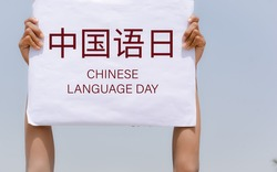 Chinese Language Day text in Chinese Language text in Chinese Language with banner in hand in sky background.