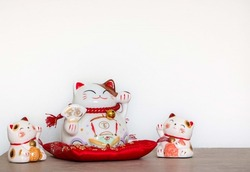Chinese lucky cat or fortune cat sitting on a red cushion with left paw raised, two small twin cats either side, characters on the big cat translate as 'Golden luck' and 'precious'