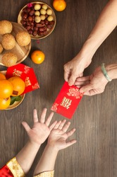 Chinese lunar new year flat lay traditional food and offering on table top. Senior women hands giving red packet to toddler boy hands.