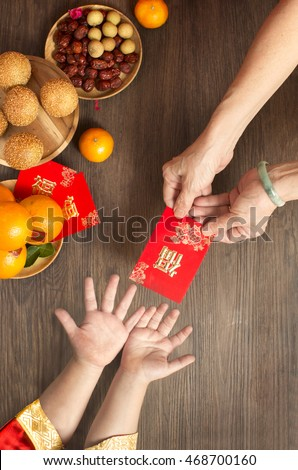Chinese lunar new year flat lay traditional food and offering on table top. Senior women hands giving red packet to toddler boy hands. #468700160