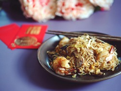 Chinese Lunar New Year lucky food longevity noodles or stir fried noodle in dark plate with chopsticks on purple background with blurred peony and red envelope with blessing word means 'good fortune'.