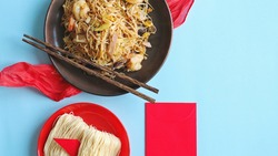 Chinese Lunar New Year lucky food longevity noodles or stir fried noodle served in dark plate with chopsticks on blue background with red fabric, blank red envelope and uncooked longevity noodles.