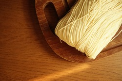 Chinese Lunar New Year lucky food uncooked Longevity Noodles or dried Chinese noodles on wooden cutting board with evening sunlight. (top view, selective focus, space for text)