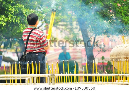 Chinese man is burning incense in the Temple