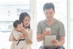 Chinese man scanning QR code with smart phone. Asian family at home, natural living lifestyle indoors.