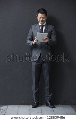 Chinese man with a tablet computer. Asian business man using digital tablet computer, leaning against a black wall.